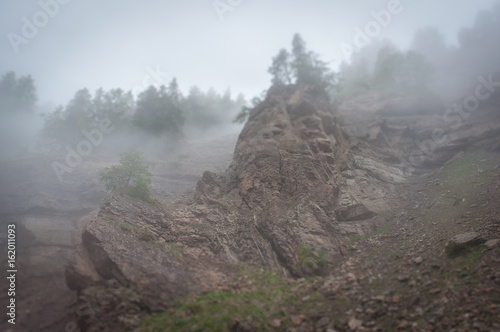 Valokuva Tilt shift effect of volcanic neck cutting red sandstones appearing from  fog in
