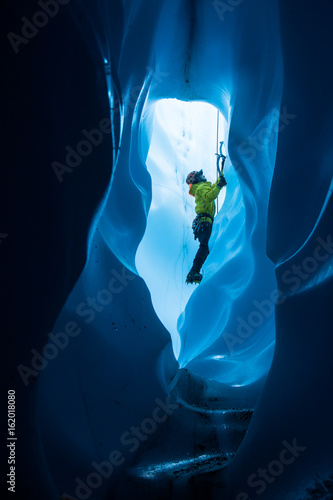 Fotografie, Obraz  Ice climber viewed through a tunnel in the bottom of a moulin on the Matanuska G