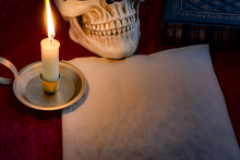 Literature And Calligraphy Concept With A Skull, Blank Old Paper Sheet With Room For Text, Vintage  Quill And A Candle Illuminating The Scene In Candlelight, With Copy Space