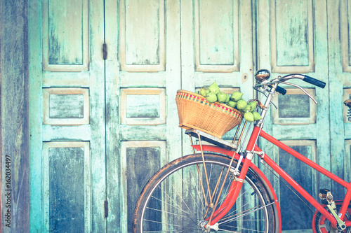 Deurstickers Fiets Hipster red bicycle in old building walls background , color if vintage tone