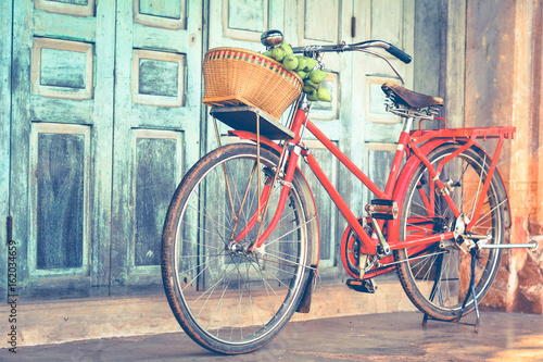 Hipster red bicycle in old building walls background , color if vintage tone