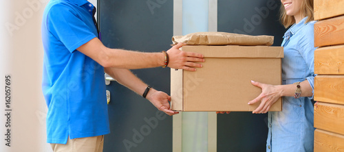 Foto Smiling delivery man in blue uniform delivering parcel box to recipient - courie