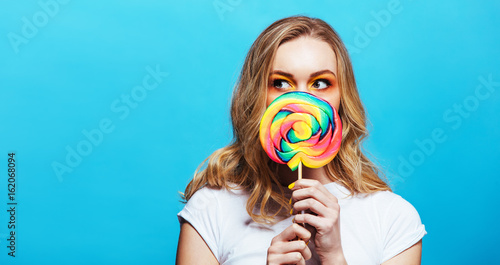 Fotografie, Obraz  Young woman holding lollipop in front of her mouth