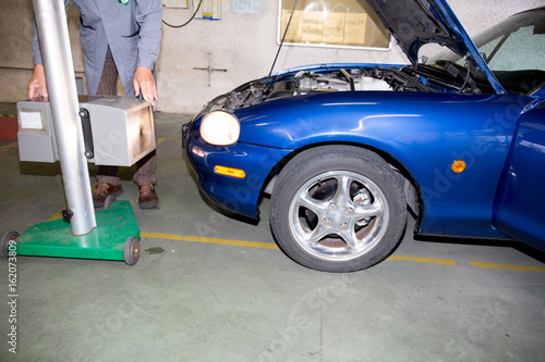 Spoed Fotobehang Snelle auto s car mechanic inspecting headlight lamp of automobile at repair service station