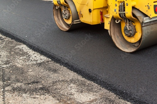 Foto New asphalt road. Road asphalt works. Construction works.