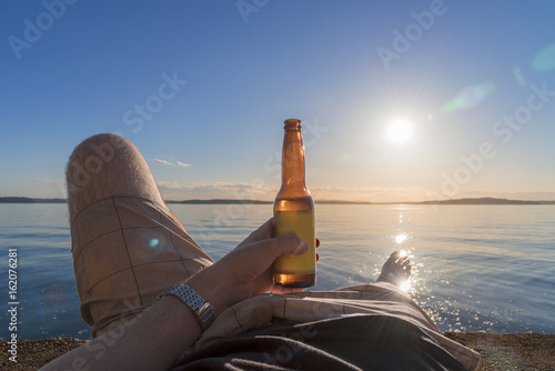 Personal perspective man laying down enjoying beer on the beach with setting sun Tablou Canvas