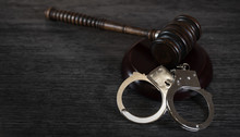 Handcuffs And Gavel On Dark Ru...
