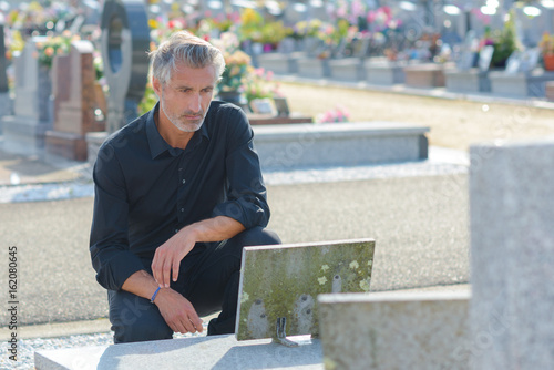 Spoed Foto op Canvas Begraafplaats man placing flowers by headstone in cemetery