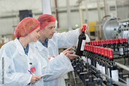Photo  scientist speaking to his colleague holding wine bottle