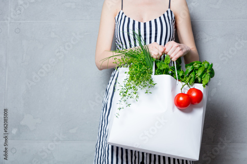 woman holding bag with organic herbs and vegetables