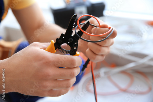Fotografía  Electrician cutting wires indoors, closeup