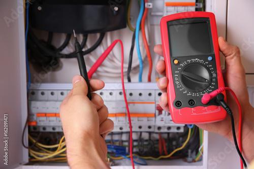 Fotomural  Electrician measuring voltage in distribution board, closeup