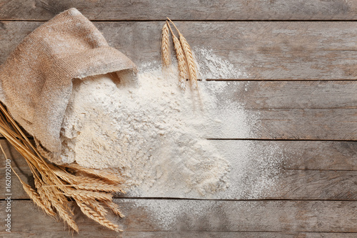 Fotografía Bag with white flour on wooden background