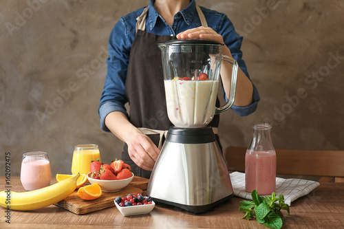 Fotografie, Obraz  Young woman preparing yogurt smoothie with berries and fruits on table in the ki