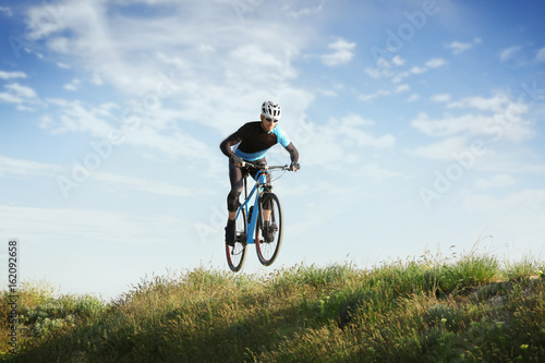 Spoed Foto op Canvas Noordzee Sporty cyclist riding bicycle in countryside