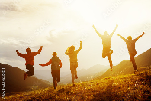 Group of happy friends run and jump