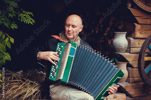 Fotografía  Mature man plays on a musical instrument accordion , is dressed in an embroidered shirt