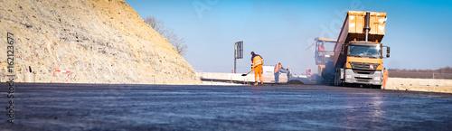 Photo Stands Monkey Aaphaltierung einer Straße, neuer Teer wird angeliefert