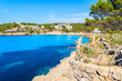 Coastal path in Cala Portinatx bay with azure blue sea water, Ibiza island, Spain