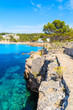 Coastal path in Cala Portinatx bay with azure blue sea water, Ibiza island, Spain