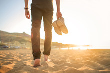 Man Walking In The Beach, He Is Holding His Pair Of Shoes.