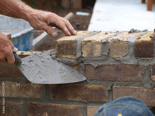 Fotografia, Obraz  In a demonstration, a master brick mason demostrates the use of a trowel in brick and mortar work