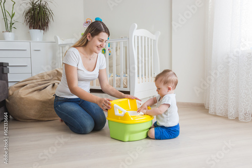 Loving mother teaching her baby boy how to use chamber pot Wallpaper Mural