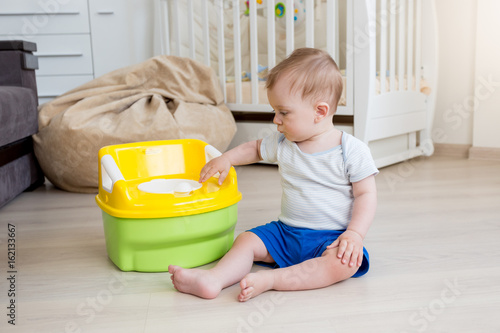 10 months old baby boy learning how to use chamber pot Canvas Print