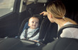 Portrait of mother and baby boy sitting in car on front seats