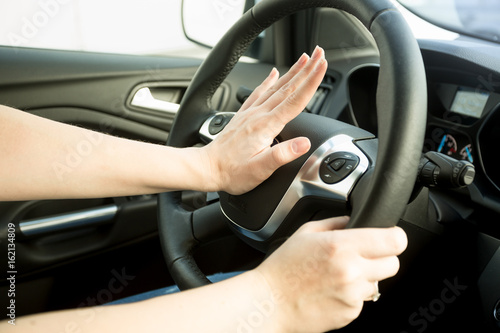 Photo Closeup image of annoyed woman driving car and honking