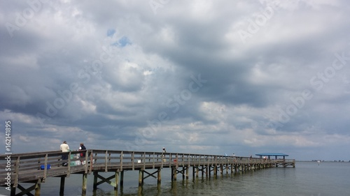 Foto auf Acrylglas Bestsellers Fishing pier with Fishermen and stormy cloudscape over the water