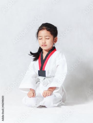 Plakat Azjatycka mała dziewczynka siedzi dla koncentraci w Taekwondo mundurze na białym tle