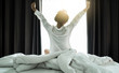 canvas print picture - Asian women wake up from sleep. are  stretch herself  in the morning on the weekend sit on the bed at luxury room in Relax and weekend concept.