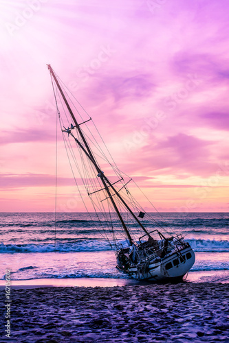 Foto op Plexiglas Purper Boat on the beach in twilight and colorful of sunset