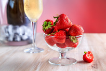 Strawberries In A Glass Vase Stands On The Table