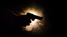 Male Hand Holding Gun On Black...