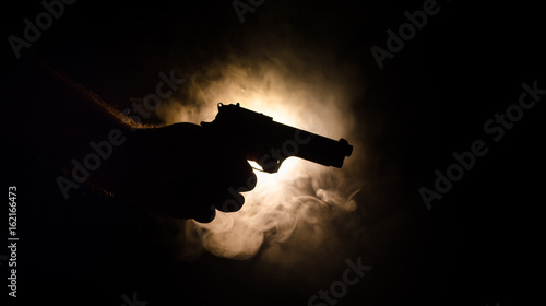 Fotografie, Obraz  Male hand holding gun on black background with smoke ( yellow orange red white )