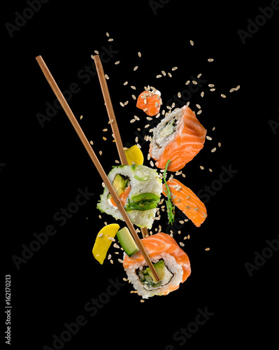 Poster Sushi bar Sushi pieces placed between chopsticks on black background