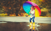 Happy Funny Child Girl With  Umbrella Jumping On Puddles In Rubber Boots  .