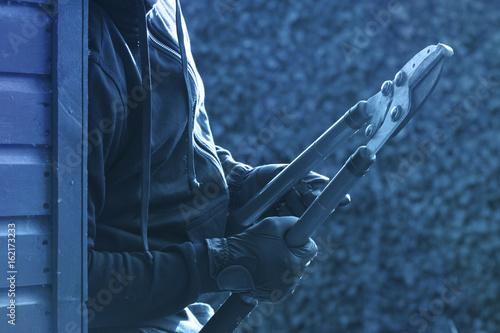 Fotografija  Einbrecher versteckt sich hinter einer Hauswand