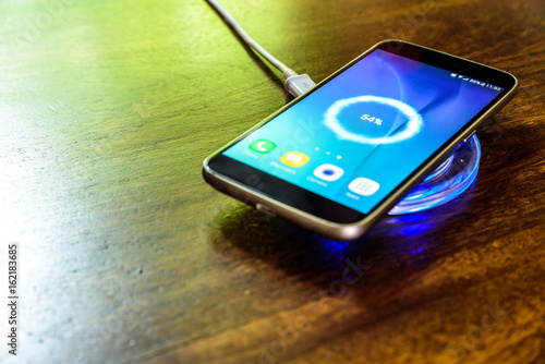 Fotografia  Smartphone charging on a charging pad. Wireless charging