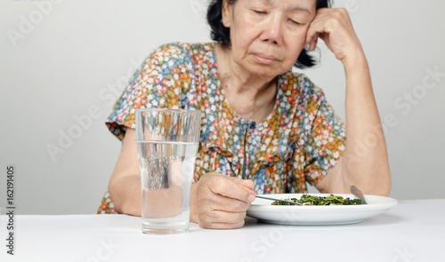Elderly asian woman bored with food Canvas Print