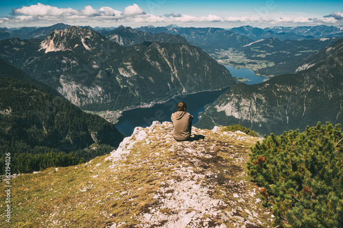Young man sitting on the edge of mountain and enjoying spectacular view Poster