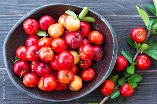 organic brazilian acerola cherry in brown ceramic plate on wooden table