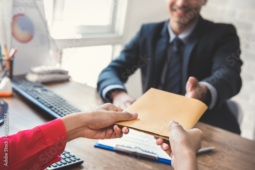 Fotografía  Businessman receiving envelope (money) from a woman while making contract