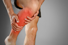 The Guy Clings To A Bad Knee. The Pain In His Leg. Closeup. The Lesion Is Highlighted In Red