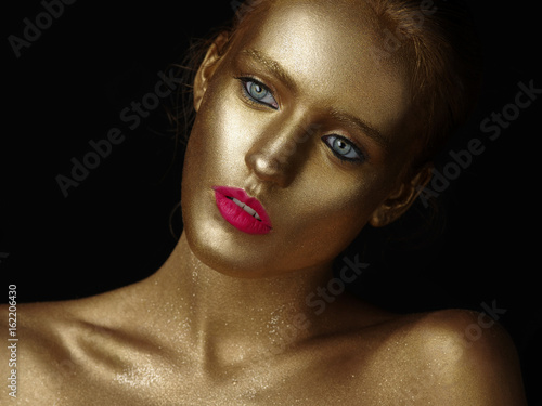 Fashionable Portrait Of A Beautiful Young Female Model With Creative Body Art Glowing Make Up Face Is Colored With Gold Paint Golden Shine Of Skin Studio Black Background Buy This Stock