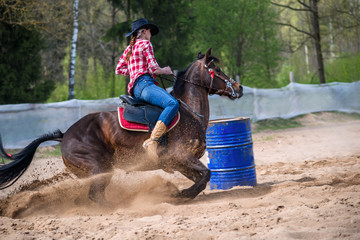 A barrel racer at a rodeo makes an explosive turn around one of the barrels, sending arena sand flying in all directions