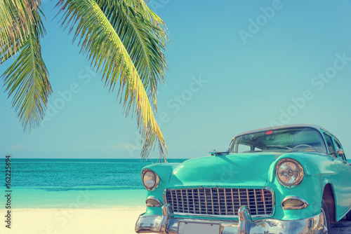 Keuken foto achterwand Vintage cars Classic car on a tropical beach with palm tree, vintage process