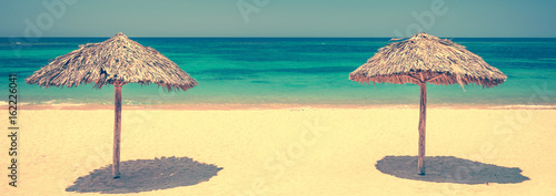 Two straw umbrellas on a beautiful tropical beach, panoramic travel background, Wallpaper Mural